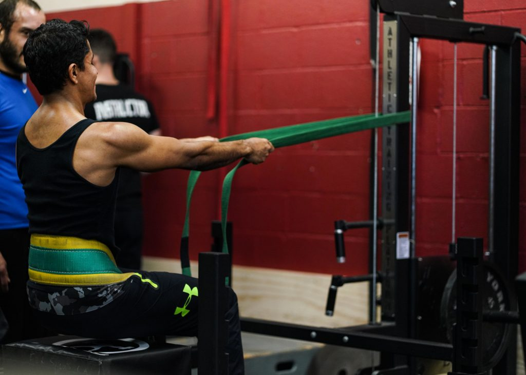 A Man Using the Belt Squat Machine